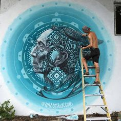 Artist Miles Toland painting a mural in Wynwood in Miami, Florida. Native American and turquoise mandala.