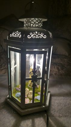 Got this lantern from joann. Drilled a hole in the bottom, the light is from the vintage ball jar lamps from joann. Cut off the jar lid hot glued it to a lil piece of wood that was a promotional magnet. Then added the moss and flowers with a hot glue gun and boom. Super girly little lantern for my patio!