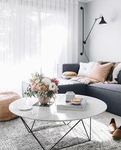 Large round white marble coffee table with black wire base, light grey textured rug, charcoal grey sofa, sheer white curtains, pale grey walls, black wall lamp