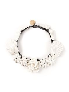 White ceramic 'Escarcha' necklace from Andres Gallardo featuring an array of white ceramic stars and flowers mounted along a heavy dark silver tone chain and a lobster claw fastened to the back.
