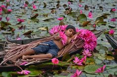 Beautiful Bangladesh: A boy sleeping on a boat full of water lilies