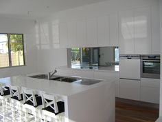 Mirror Splashback Kitchen with white push open doors no handles very simple sleek and have coloured vases etc