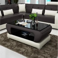 Description Use this leather coffee table to add style and practical functionality to any formal room. A combination of solid wood, glass, and leather makes this contemporary coffee table an attractive piece in any contemporary environment. This table'swhite leather encasement, while its black glass top offers a bold,