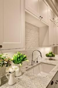 Lovely creamy white kitchen design with shaker kitchen cabinets painted Benjamin Moore White Dove, Kashmir White Granite counter tops, polished nickel modern faucet and Vetro Neutra Listello Sfalsato Glass Mosaic- Bianco tiles backsplash.