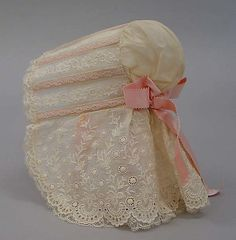 Lightweight cotton slatted sun bonnet. Ayrshire-like embroidery on the cape, insertion from ear to ear, plain tip, silk ribbons inside and back. [The slats may be wrapped in the same silk.] MET