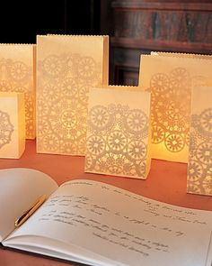 Guest Table DIY - Give the decorations at your wedding reception the romantic look of lace. The intricate patterns shining through these luminaries (paper-bag lanterns illuminated by votive candles) are courtesy of doilies glued inside.