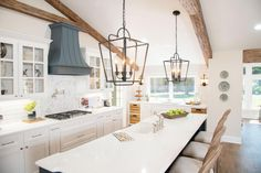Knowing that the exposed beams would warm up the space, I went with white cabinetry, white countertops and white backsplash. Accents like black iron pendants, navy details and wooden beams finish this room up perfectly.