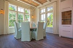 source: Pizitz Home and Cottage  Cottage dining room with rustic wood ceiling accented with white wood beams punctuated with antique brass chandelier over round gray dining table surrounded by seafoam green slipcovered dining chairs. Seaside dining room features tongue and groove walls paired with off-white pinch-pleat curtains as well as glass-front wine fridge.