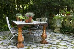 Moss grows in the cracks of the cobblestone patio, where vintage elements combine to make a table