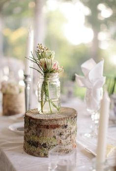 Mason jar with simple flowers, sitting atop rustic, mossy tree cutting as wedding centerpiece.
