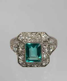 PLATINUM, EMERALD, AND DIAMOND RING the open-work filigree setting bezel-set with a step-cut emerald measuring approx. 7.40 x 5.75 x 3.60 mm., framed by twenty-two full and single-cut diamonds weighing approx. 0.65 cts. total; 3.22 dwts.; size 5 1/2