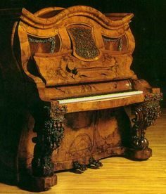 Napoleon Hat Shape Piano, one of the earliest surviving upright pianos, commissioned by Queen Victoria in 1853, made in England as a wedding gift for Napoleon III, a nephew of Napoleon Bonaparte. Made of walnut wood, the piano has beautifully carved decorations of roses and figs on its legs and pedals