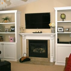"Bookshelves around fireplace for ""built ins"". Store media equipment, games and DVDs in cabinets. Shelves for display."