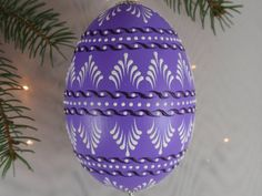 This is a small goose egg pysanka. It is painted purple and decorated with white and dark purple wax. To create this egg, I use the pinhead method also