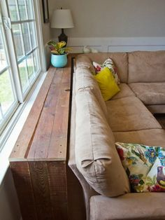 A long, narrow wooden table between the back of the sofa and the wall -- instead of a coffee table! Love how the table (and everything on it) stays completely out of the way....