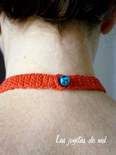 Foto1 Sobre una base de croché en color rojo he cosido yoyos de tela, rosetas en color rojo y turquesa, lentejuelas y cristal de swarovski. El collar se cierra en la nuca con un cascabel de color azul.