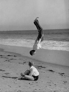 Acrobat/Actor, Russ Tamblyn Doing a Flip on Beach with Movie Actress Venetia Stevenson Watching Him