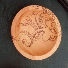 This six inch bowl is made from beech wood and features an octopus design done in pyrography (woodburning). This is one of my most popular designs. The tentacles of the octopus are wrapped around the outside of the bowl, giving it the appearance of climbing out of the bowl. This is a made to order item. Please allow 4-8 business days for completion. Due to the handmade process of burning, there may be slight variation from the design pictured. The bowl is coated with a food safe beeswax…