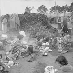 THE LIBERATION OF BERGEN-BELSEN CONCENTRATION CAMP, APRIL 1945. Women inmates prepare food in the open air, using the boots of the dead (which can be seen piled up in the background) as fuel for their fires.