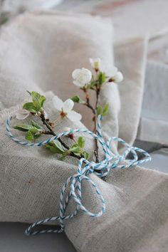 Natural neutral linen napkins tied with blue and white baker's string and pretty white blossom brnach tucked inside - perfect for a spring table
