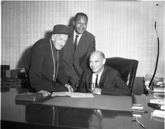 Mayor Tom Bradley (center) with entertainer Jimmy Durante (first left) and Supreme Court Judge Vincent Dalsimer (seated). The men are in an office. Photo by Harry Adams.
