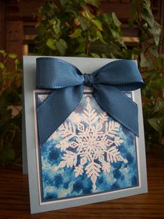 This is a Magic Snowflake indeed!  Love the use of nontraditional blue for both the ribbon and the muted colors of the backdrop, which you can create with alcohol and heat.  Very pretty handmade Christmas card.