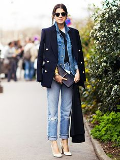 Leandra Medine of Man Repeller wearing cuffed, boyfriend jeans, a menswear inspired double-breasted blazer over a denim jacket, and white heels