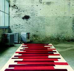 Modern white and red pure wool rug with irregular striped pattern.