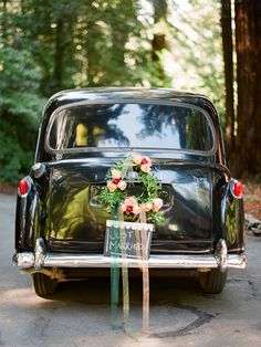 Floral wreath, colourful streamers and chalk board just married sign on wedding getaway car