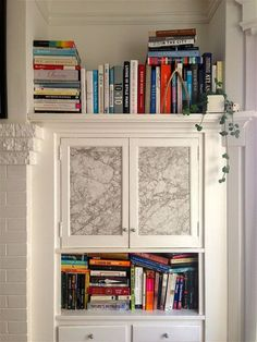 6 Unexpected Uses For Wallpaper: Taped up marble wallpaper hides warped glass in Christiana's built-in cabinet.