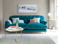 Sofa in teal velvet fabric in a living room with a coffee table