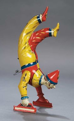 *GERMAN LITHOGRAPHED TIN MECHANICAL :  The lithographed tin clown w/ brightly-designed costume in red + yellow has hinged arms + is balanced upon them. When wound, he walks on his hands, c. 1920