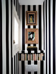 Fearless bold stripes in a tiny bathroom. (Aren't the gold framed portraits a luxe touch?)