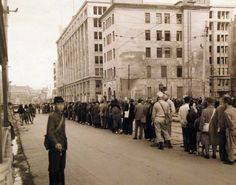 80-G-264851: Japanese Surrender, August-September 1945. Scene at Sasebo, Kyushu, Japan, shows people lined up for trolley car on Ginza Street. Photographed by crewmember of USS Chenango (CVE 28), released October 19, 1945.