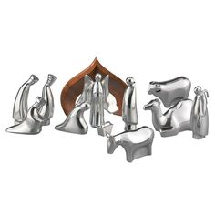 """The 12-Piece Nativity Collection is a modern, yet timeless portrayal of the world-recognized Holy Family the night of Jesus' birth. With heads bowed, Mary and Joseph gaze affectionately at baby Jesus lying in his manger in front of a beautifully arched crèche of carved wood. Onlookers include the <a href=""""http://www.nambe.com/namb/ctl10101/cp59110/si3418991/cl1/three_wise_men"""" title=""""Namb"""
