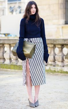 A turtleneck sweater with oversized sleeves is worn with a striped slit skirt, gray pumps, and a croc clutch bag