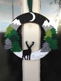A stunning wreath for Winter inspired by the scenery of Alaska. The wreath features mountains and pine trees as well as a large stag and an arctic fox.