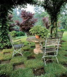 The owner of this Pennsylvania home's garden is canopied by a trumpet vine, golden hops, and rose-bowered pergola, with concrete pavers laid down checkerboard style.