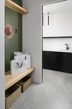 Clean lines and calming hues of sage wall color in this contemporary mud room / drop zone for the ultimate home organization space.  #MudRoom #HomeOrganization #MinimalDesign