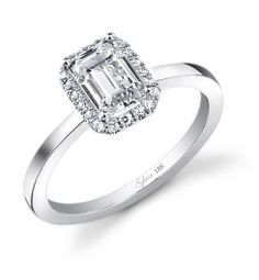 This Magnificent 18K white gold diamond engagement ring features a 1.25 carat emerald cut center diamond. Accentuated by surrounding round diamonds and designed to enhance the center diamond, contains a total 0.28 carats.