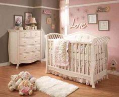murs gris et roses et mobilier blanc dans la chambre bébé fille