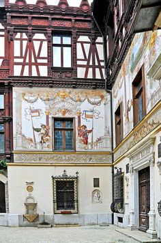 Peles Castle´s courtyard in Bramantes style with a fountain in the middle, in the Renaissance style. The courtyard facades are painted with elegant pictures and designs.