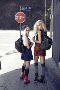 2 cô gái phong cách grunge trang phục váy ngắn kẻ caro, quần tất len đến đùi gối, bốt da cổ thấp nhiều màu, đeo balo  và trang điểm đậm, kẻ mắt đen cá tính