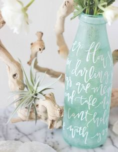 DIY ~ add frosted glass spray paint to a glass bottles or vases to recreate this idea! Trace words with a pencil and use an acrylic white paint pen to add the calligraphy. Frosted Glass Spray, Deco Marine, White Paint Pen, Wine Bottle Crafts, Wine Bottles, Bottle Bottle, Vase Centerpieces, Wedding Centerpieces, Mason Jars