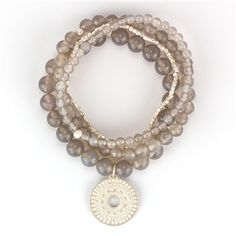 Grey onyx beads of various sizes and sterling silver beads layer to make an opulent 4-strand bracelet. Combined with a mandala pendant, this bracelet is a powerful portent of spiritual transformation.