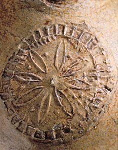 "Title:  Bellarmine jug Date:  ca. 1672 Place:  Chelsea (London, England) ? Format:  Dark buff stoneware / salt glaze / H.: 8 7/8"" (22.5 cm); Diam. (body): 5 1/4"" (13.3 cm) Description:  Image Description: Detail: stylized flower"