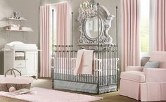 Staring off with this elegant yet subtle nursery, adorned in light pink tones around grey. Natural hardwood flooring supports metal crib under ornate mirror, with white changing table and shelving in corner.