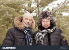 Portrait of middle-aged couples among the branches of young pine trees in winter