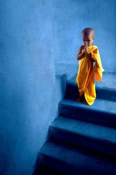 Little yellow children monk prays on blue stairs