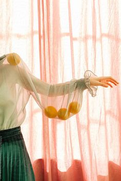 colorful photograph of woman wearing sheer green blouse with lemons in the sleeve in front of pink sheer curtains. / sfgirlbybay